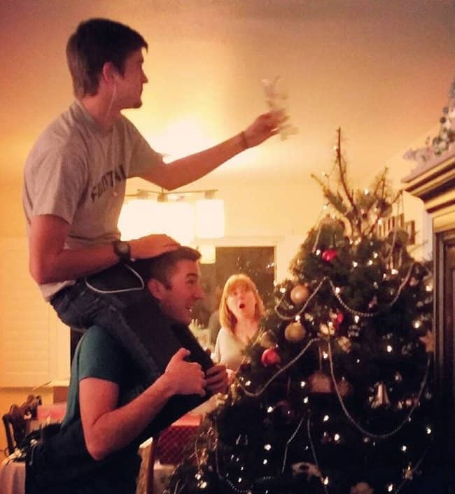 brothers-putting-the-star-on-the-top-of-christmas-tree