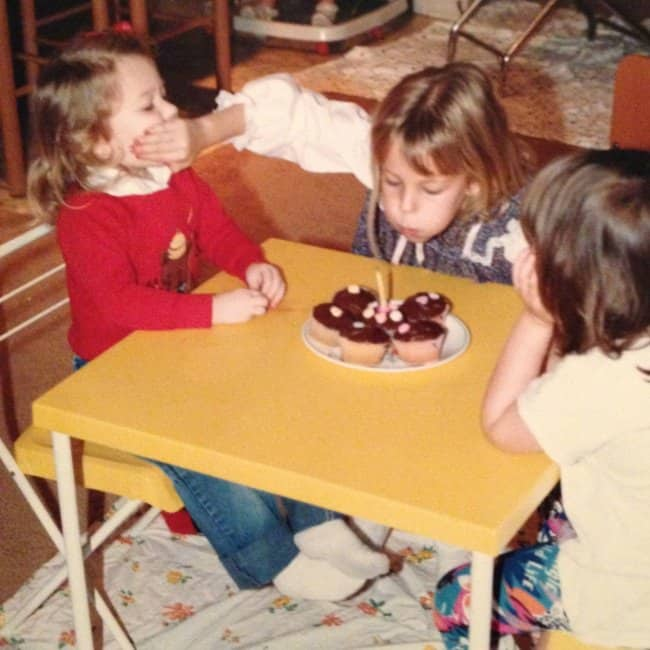 girl-covering-sisters-mouth-to-blow-the-candle