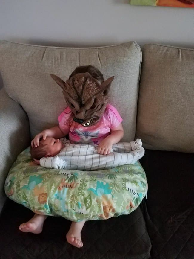 little-girl-wearing-a-wolf-mask-while-holding-her-baby-brother