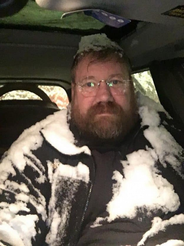 man-covered-in-snow-inside-a-car