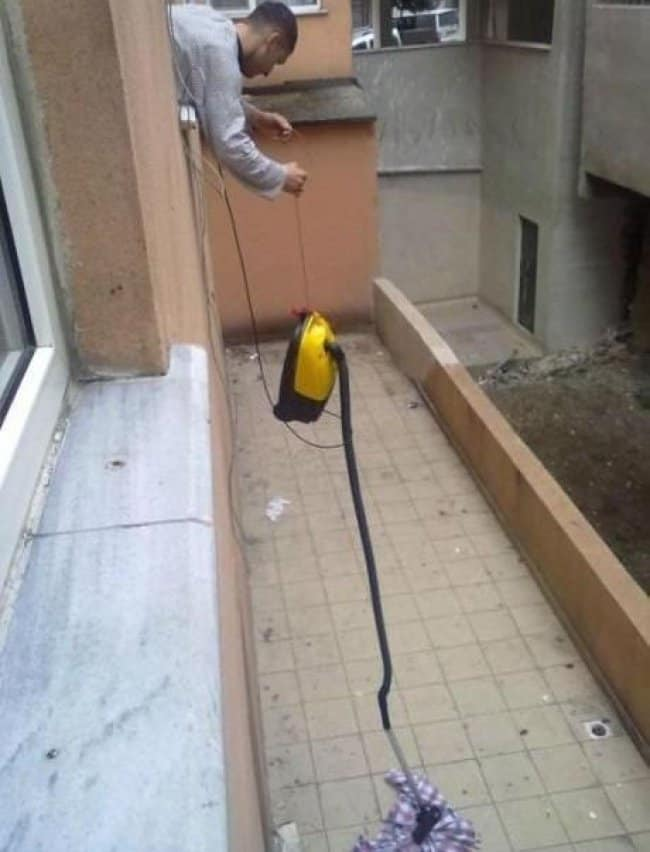 man-using-a-vacuum-to-pick-up-shirt-outside-the-building
