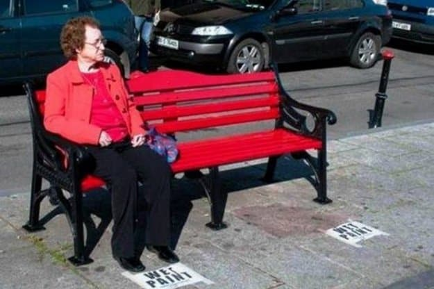 old-woman-sitting-down-on-a-newly-painted-bench