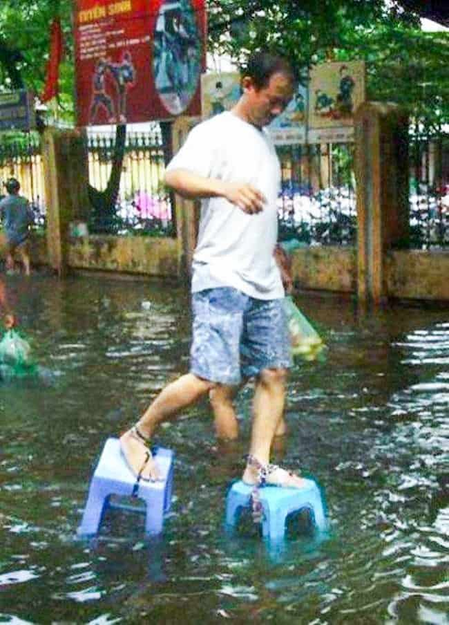 tying-chairs-to-feet-as-shoes-for-walking-a-flooded-street