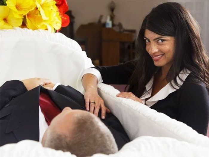 girl-devilish-smile-with-man-in-the-coffin-weird-stock-photos