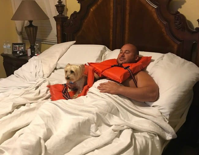 man-and-dog-wearing-vests-in-bed