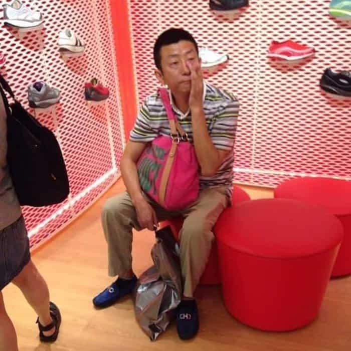 man-carries-purse-while-waiting-men-hate-shopping