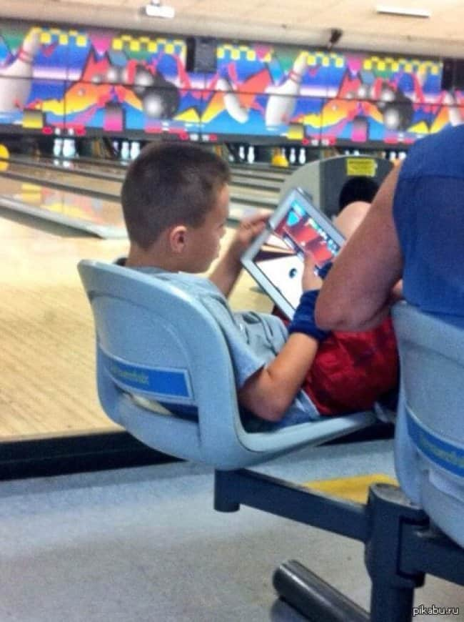 playing-a-bowling-game-in-tablet-while-at-a-bowling-alley