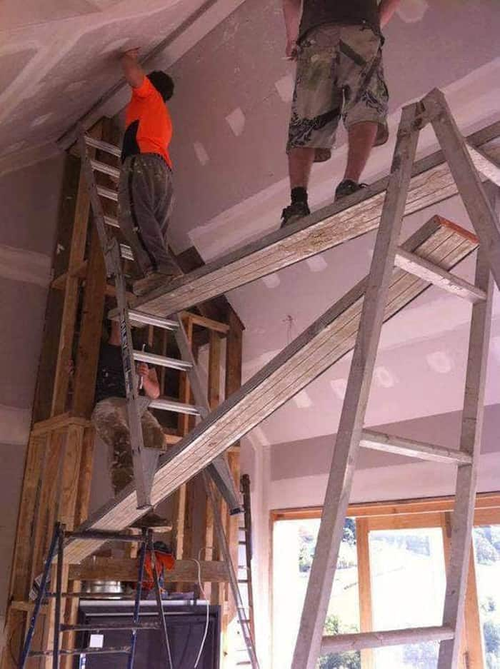 stand-platform-made-from-ladders-and-metal-planks-audacious-workers