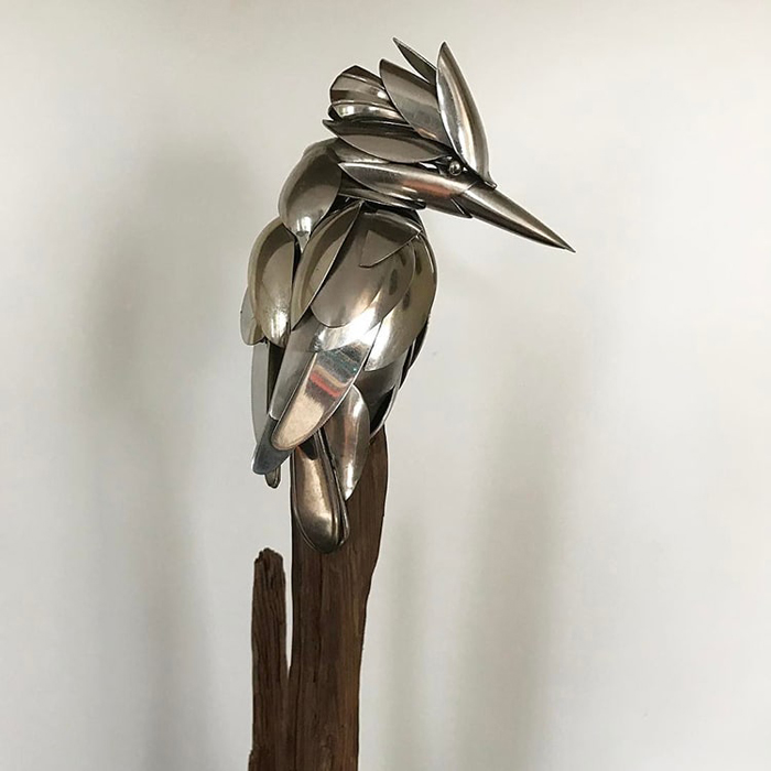 metal bird sculpture perched on wood