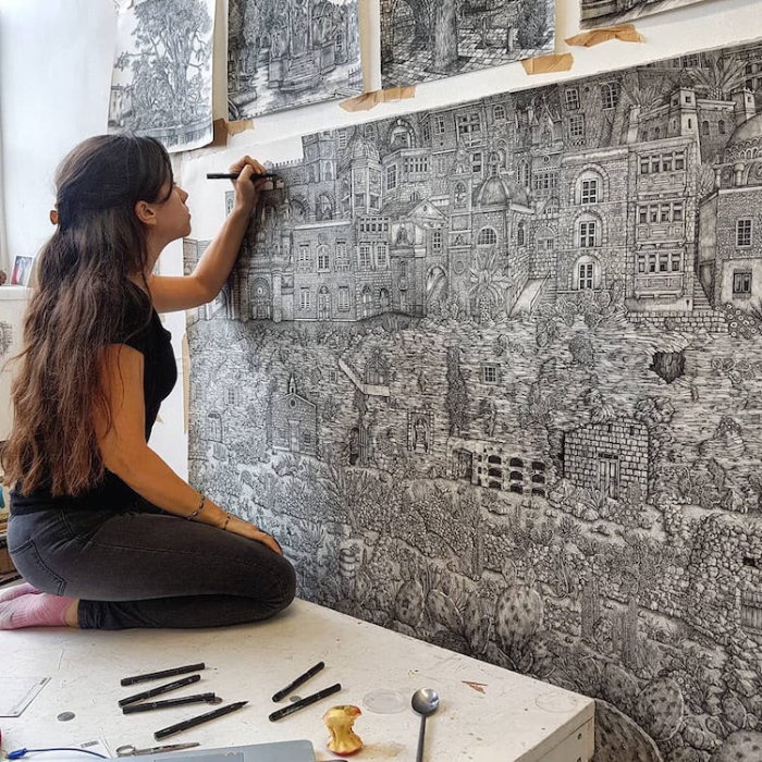 Olivia Kemp while creating a detailed pen drawing