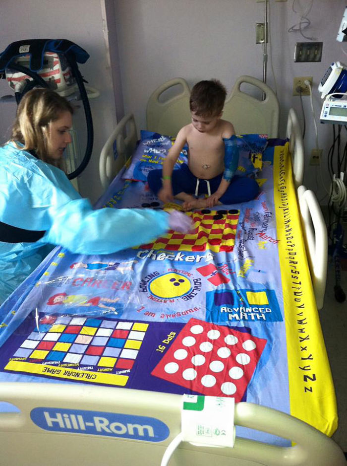 hospitalized boy playing board game bed sheets