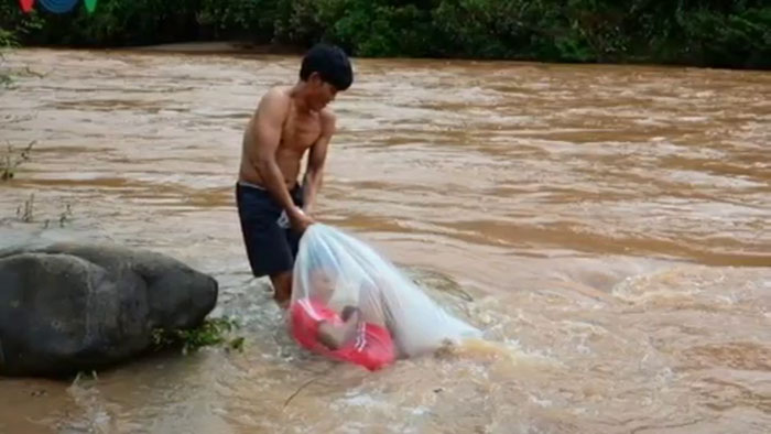 man dragging kid in plastic bag cross river