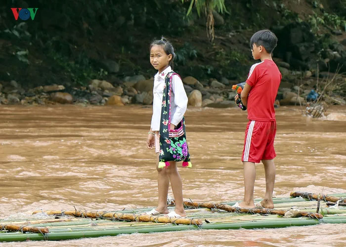 vietnamese schoolkids crossing river bamboo rafts