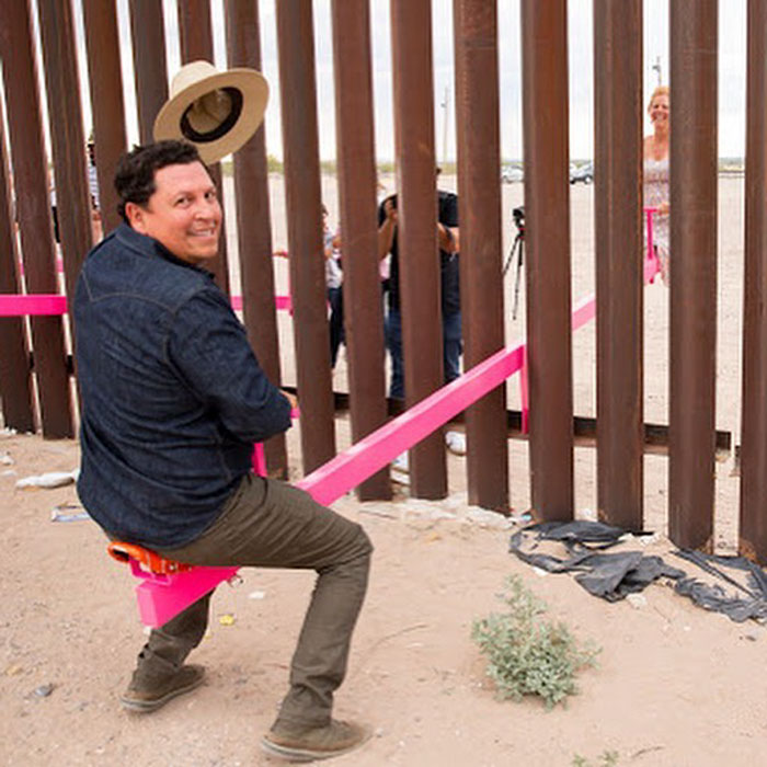 adult playing seesaw in the us mexican border