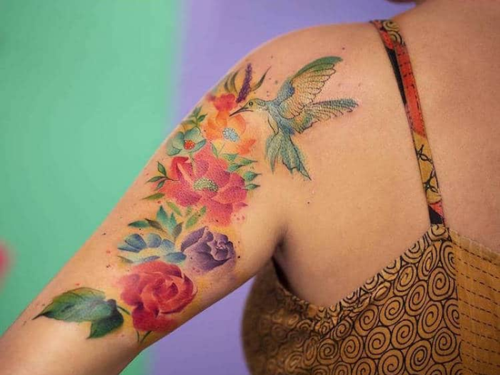 bright flowers with bird upper arm best floral tattoo artists