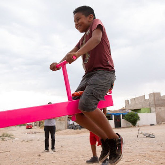 child happy seesaw in the us mexican border