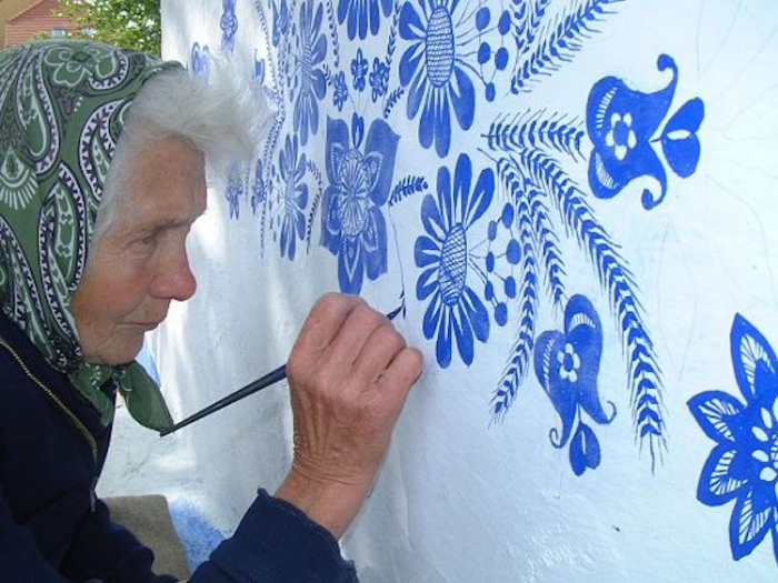 close up grandma paints houses louka