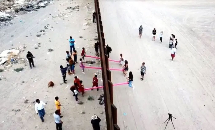 happy people playing seesaw in the us mexican border