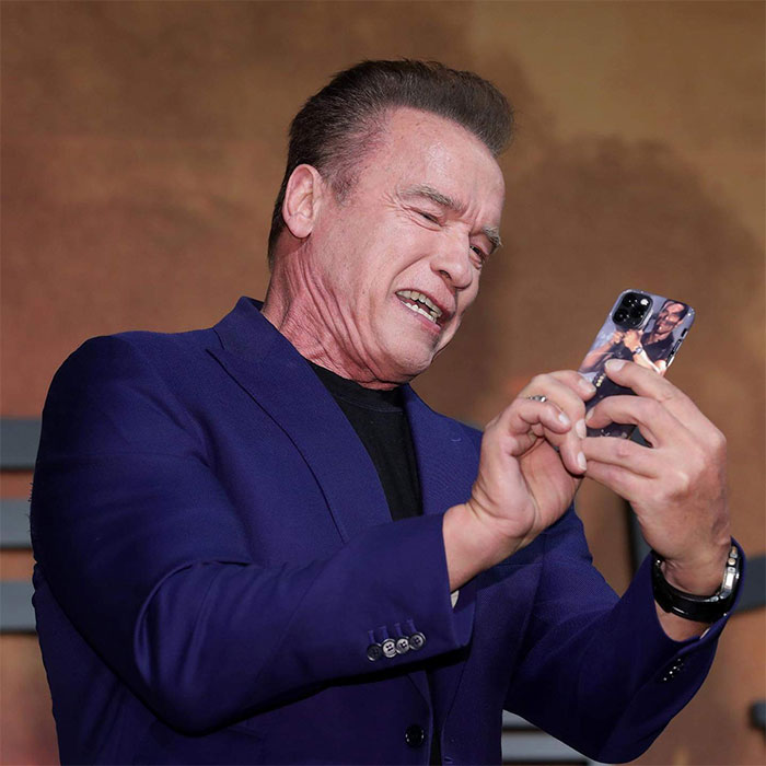 Arnold Schwarzenegger Holding an iPhone 11 Pro with an Arnold Schwarzenegger Rocket Launcher Case