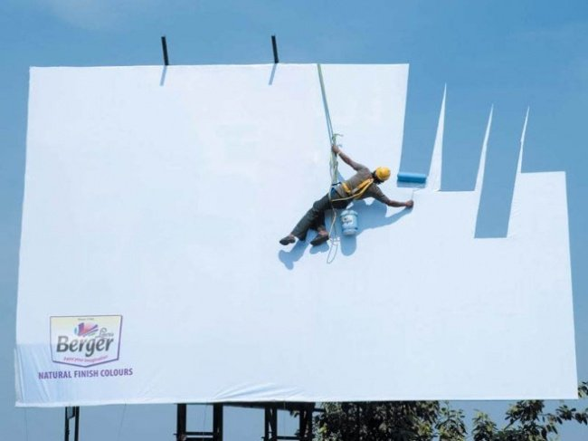 Berger Paints Advertisement Featuring a Man Painting the Billboard with Skyblue