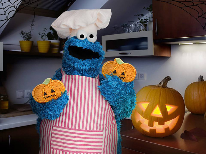 Cookie Monster in Apron and Toque Holding Two Pumpkin Cookies