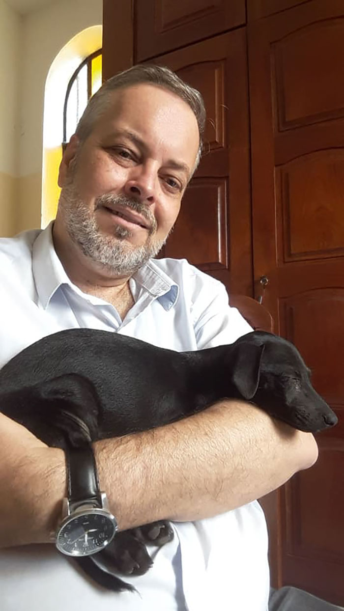 Father João Paulo Araujo Gomes Carrying a Black Stray Dog