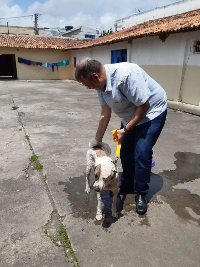 Father João Paulo Araujo Gomes Petting a Stray Dog on a Leash