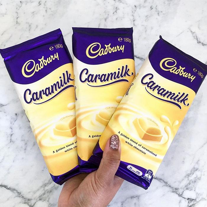 Hand Holding Three Packs of Cadbury's Caramilk