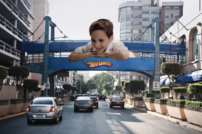 Hot Wheels Billboard Featuring a Boy Looking at Actual Road Traffic