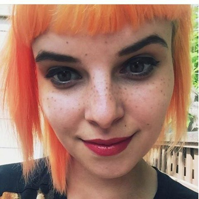 Lady with Short Orange Hair and Freckle Tattoos on Face