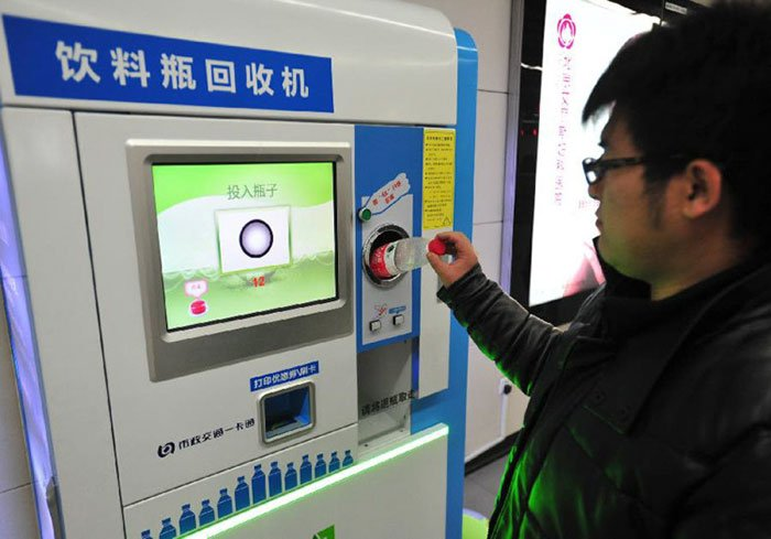 Man Inserting a Plastic Bottle to a Payment Terminal at Beijing Subway