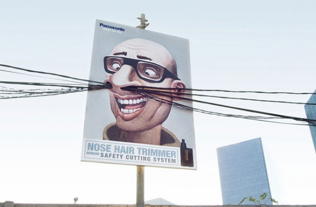 Panasonic Nose Hair Trimmer Billboard Featuring a Man with Cable Wires as Nose Hair