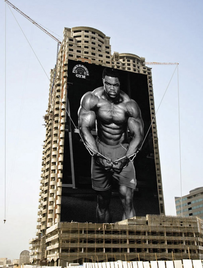 Powerhouse Gym Advertisement Featuring a Man Doing Cable Flyes on a Double-craned Construction Site