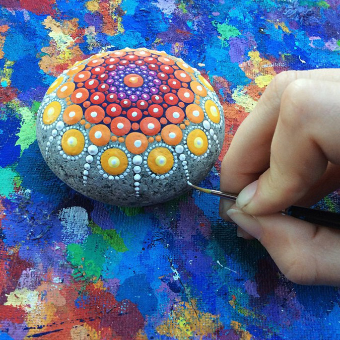 artist paints one of her mandala stones