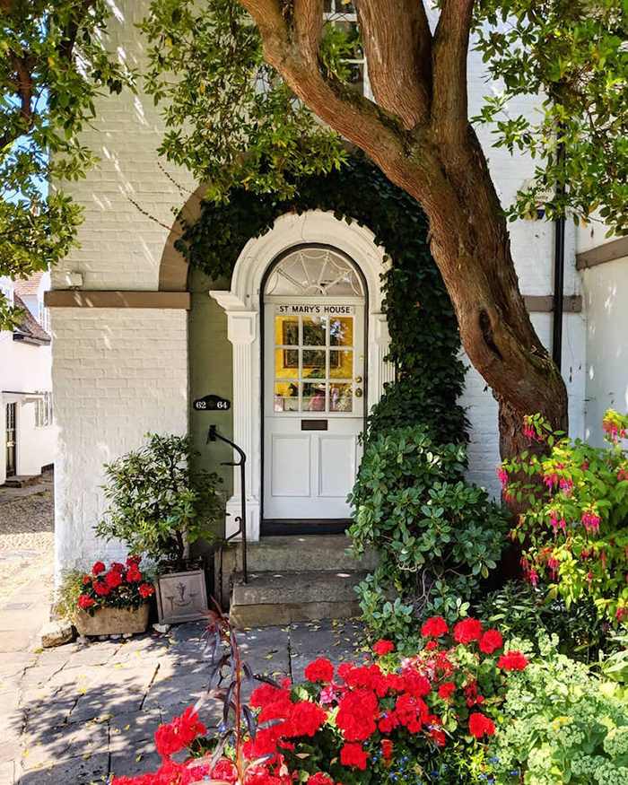colorful front doors white framed by lush greenery