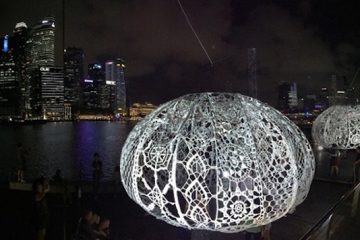 giant crochet sea urchins lit up at night