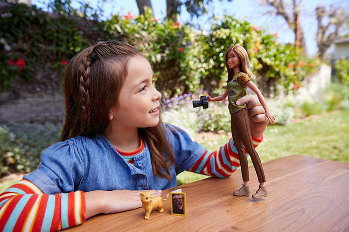 little girl plays with barbie photojournalist