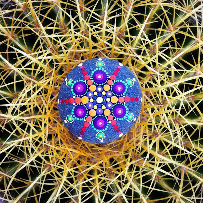 mandala stones placed atop cactus