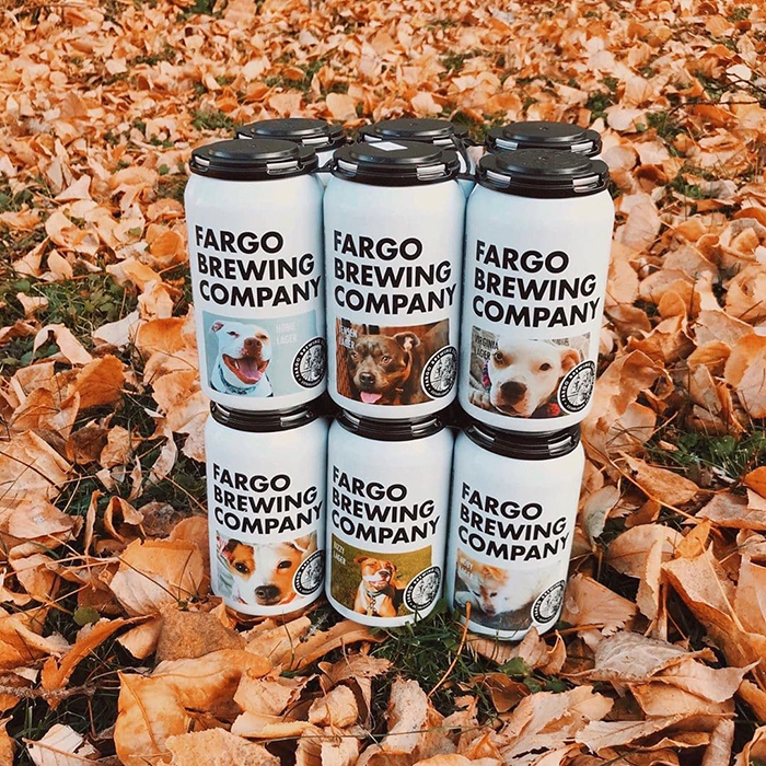 Fargo Brewing Company Beer Cans Featuring Adoptable Dogs on Autumn Leaves