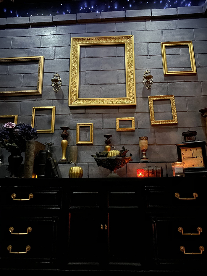 Black Cabinets and Gold Frames Hanging on the Wall