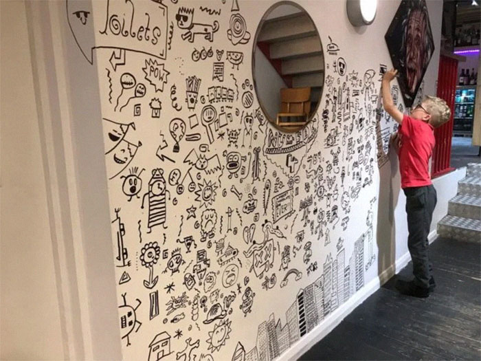 Joe Whale Doodling on a Wall with Einstein's Photo