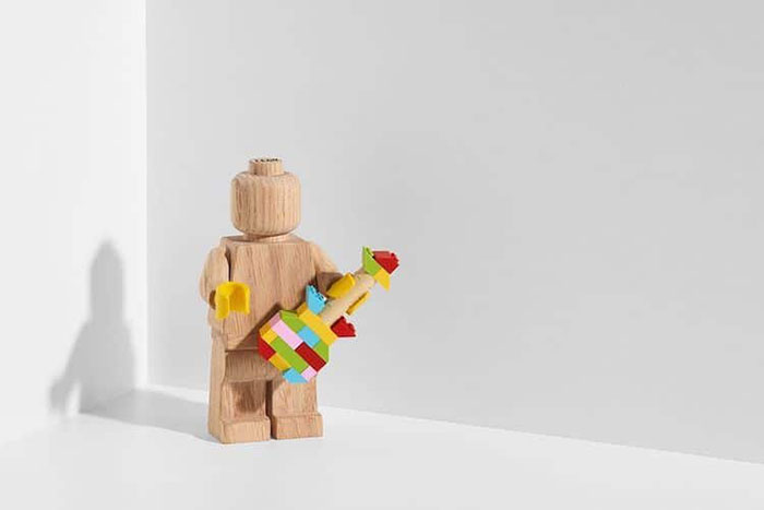 LEGO Wooden Figure Holding a Colorful LEGO Tower with Its Left Hand