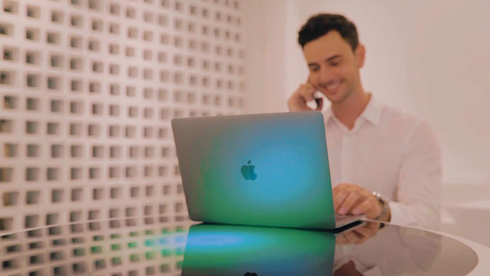 Man Working on His Macbook on Top of a Coosno