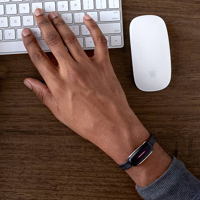 Man's Hand Wearing a Vibrating Bracelet While Working