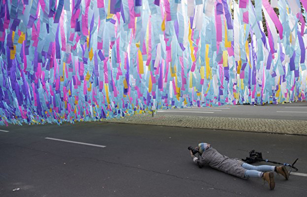 Photographer lays on road to take photos of the art installation