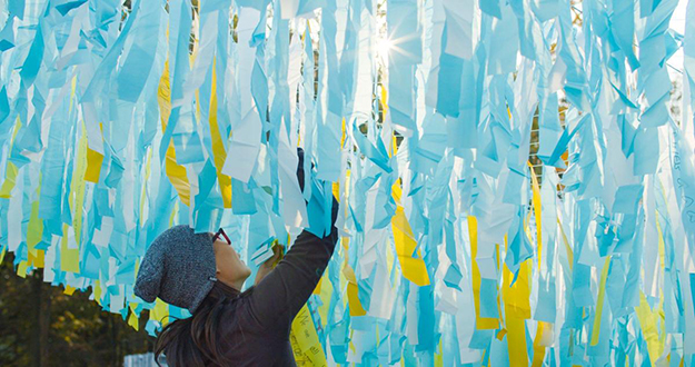 a poetic kinetics member oversees the yellow white and blue streamers