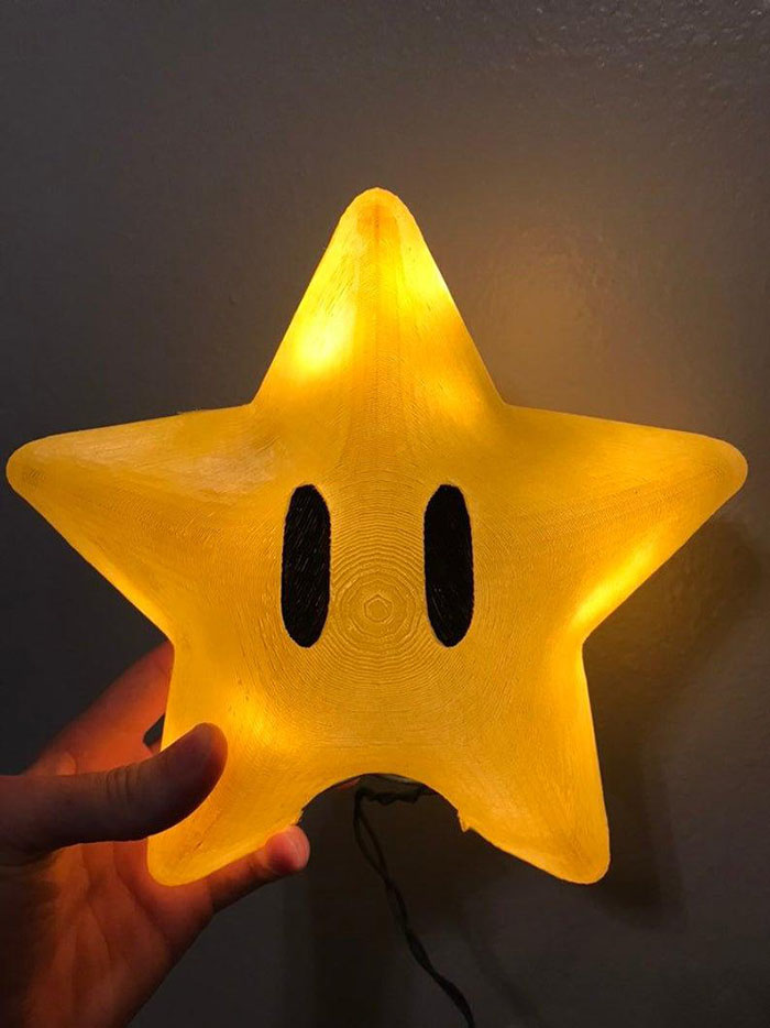 artist holds the large super mario power star tree topper