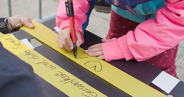 child writing on streamer used in the visions in motion art installation