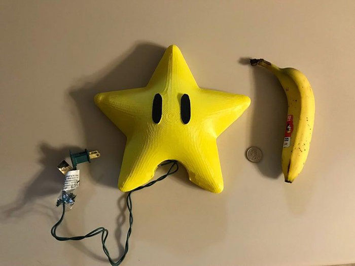 large super mario power star tree topper with banana and coin for scale