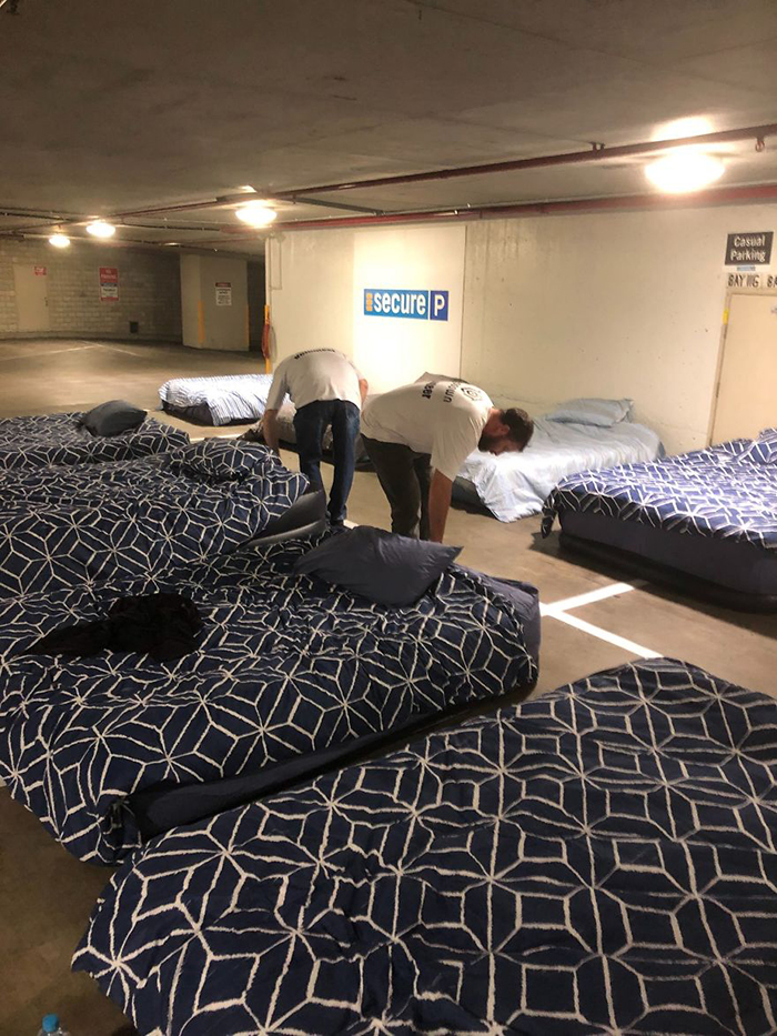 volunteers setting up beds on empty parking lot